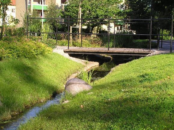 Bäck rinner under träbro mellan två gräsmattor