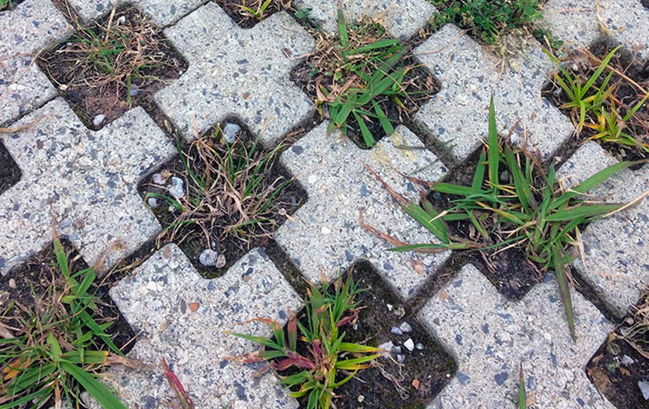 mark med kryssformade betongstenar med gräs emellan